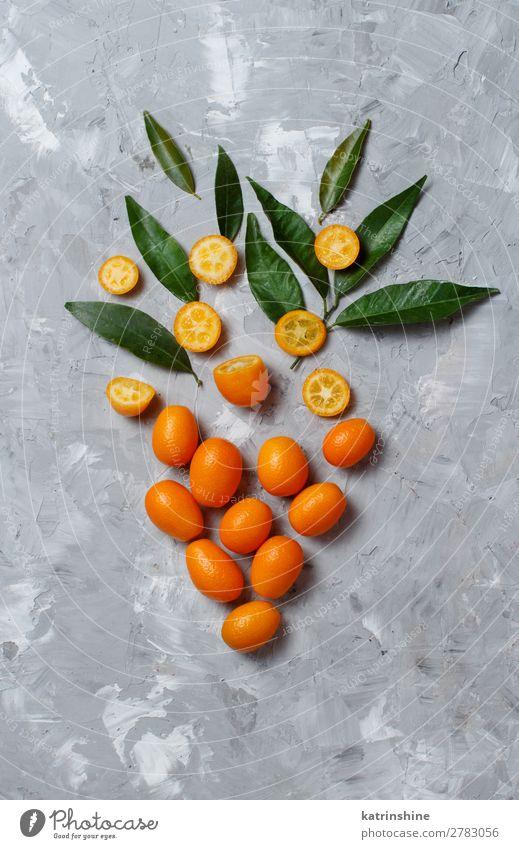 Kumquat-Früchte auf grauem Hintergrund Frucht Dessert Ernährung Vegetarische Ernährung Diät exotisch Menschengruppe Blatt frisch natürlich oben saftig gelb