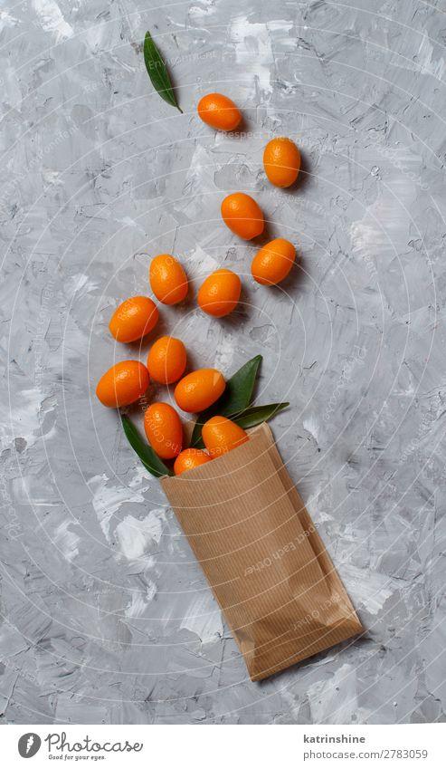 Kumquat-Früchte auf grauem Hintergrund Frucht Dessert Ernährung Vegetarische Ernährung Diät exotisch Menschengruppe Blatt Papier frisch natürlich oben saftig