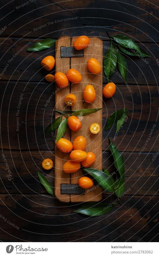 Kumquat-Früchte auf dunklem Holzgrund Frucht Dessert Ernährung Vegetarische Ernährung Diät exotisch Menschengruppe Blatt dunkel frisch natürlich oben saftig