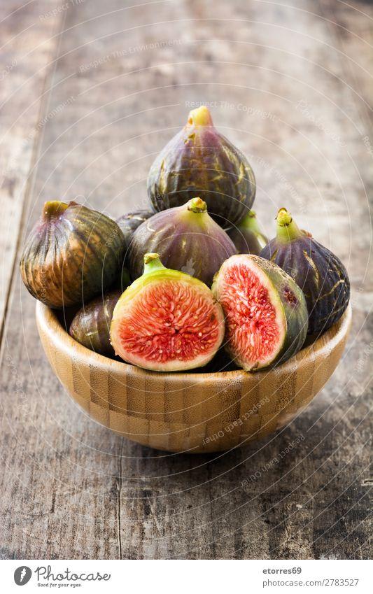 Ein paar Feigen in einer Schüssel auf altem Holzgrund Frucht Lebensmittel Gesunde Ernährung Foodfotografie exotisch süß roh rot frisch tropisch Scheibe