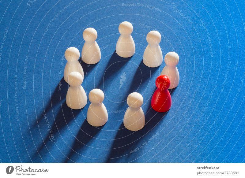 Eine rote Spielfigur steht gemeinsam mit weißen Spielfiguren in einem Kreis auf blauem Untergrund Spielen Menschengruppe Holz Freundlichkeit Akzeptanz Schutz