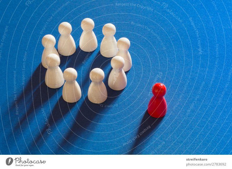 Rote Spielfigur steht außerhalb von einem Kreis aus weißen Spielfiguren auf blauem Untergrund Spielen Menschengruppe Spielzeug Holz wählen Traurigkeit rosa