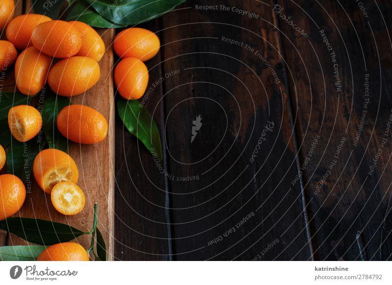 Kumquat-Früchte auf dunklem Holzgrund Frucht Dessert Ernährung Vegetarische Ernährung Diät exotisch Menschengruppe Blatt dunkel frisch natürlich saftig braun