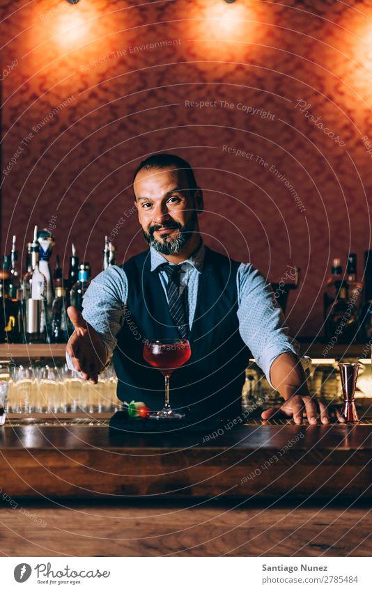 Barman macht Cocktails im Nachtclub. Schüttler Barmann Barkeeper Kellnern Mann Porträt Porträtmalerei rühren Mixologe Hinzufügen Alkohol Aufschlag Business Club