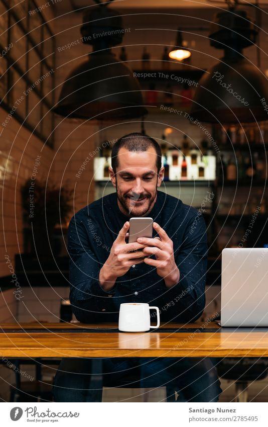 Geschäftsmann mit seinem Handy in der Cafeteria. Mann Kaffee Freundlichkeit Porträt Jugendliche Mensch Lifestyle Business Mitteilung PDA Mobile benutzend Text