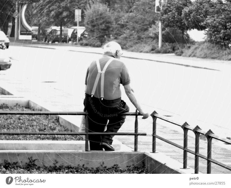 Alter Mann, wartend Mann Senior Straße warten sitzen Bürgersteig Zaun strahlend Überbelichtung gleißend Hosenträger Vorgarten Männlicher Senior