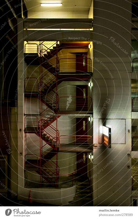 Parkhaus Gebäude Mauer Wand Treppe Fassade dunkel eckig grün rot schwarz weiß Außenaufnahme Menschenleer Nacht Kunstlicht Licht Schatten Kontrast