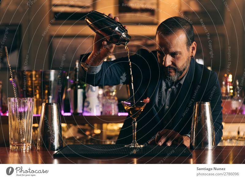 Barman macht Cocktails im Nachtclub. Schüttler Barmann Barkeeper Kellnern Mann rühren Mixologe Hinzufügen Alkohol Business Club trinken professionell Pub