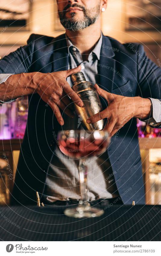 Barman macht Cocktails im Nachtclub. Schüttler Barmann Barkeeper Kellnern Mann rühren Mixologe Hinzufügen Alkohol Business Club trinken professionell Porträt