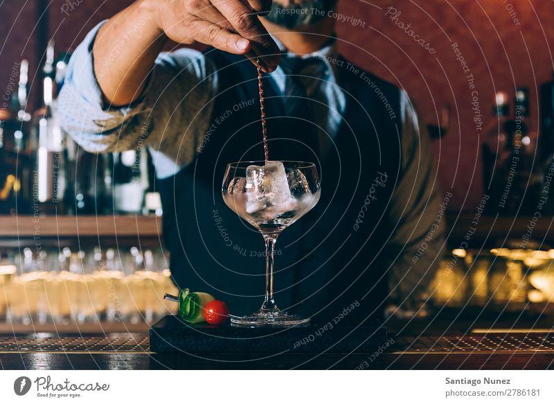 Barman macht Cocktails im Nachtclub. Schüttler Barmann Barkeeper Kellnern Mann rühren Mixologe Hinzufügen Alkohol Business Club trinken professionell Frucht Eis