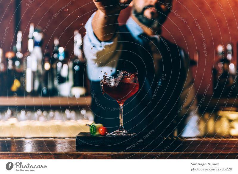 Barman macht Cocktails im Nachtclub. Schüttler Barmann Barkeeper Kellnern Mann rühren Mixologe Hinzufügen Alkohol Business Club platschen Tropfen trinken