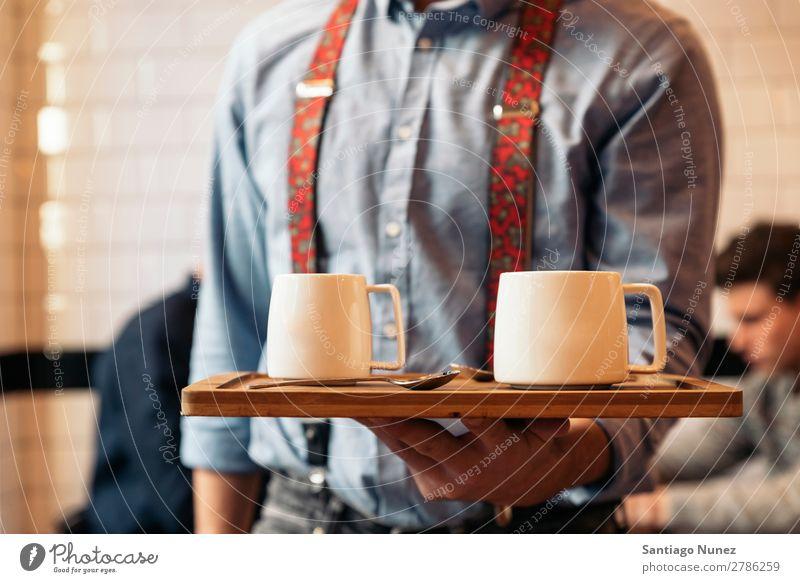 Der Kellner hält ein Tablett mit Kaffee. Kellnern Kantine Portion Café Barista kaufen Angebot Tasse schließen Aufschlag nach oben Server Jugendliche Aussicht