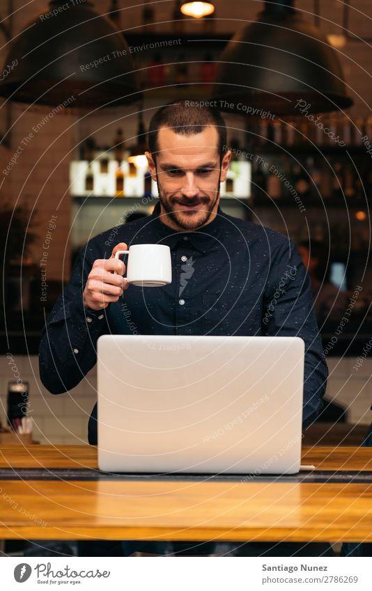 Geschäftsmann mit seinem Laptop im Coffee Shop. Mann Kaffee Freundlichkeit Porträt Jugendliche Mensch Lifestyle Business Mitteilung PDA Handy Mobile benutzend