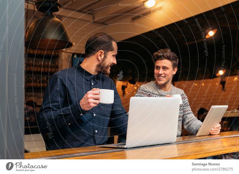 Freunde, die Tablett und Laptop benutzen. Mann Kaffee Freundschaft Jugendliche Teamwork Menschengruppe Lifestyle PDA Tablet Computer benutzend Text Notebook