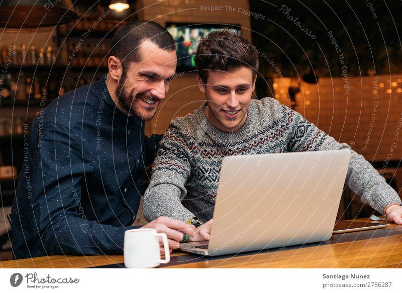 Freunde, die Handy und Laptop benutzen. Mann Kaffee Freundschaft Jugendliche Teamwork Menschengruppe Lifestyle PDA Mobile Mitteilung benutzend Text Computer