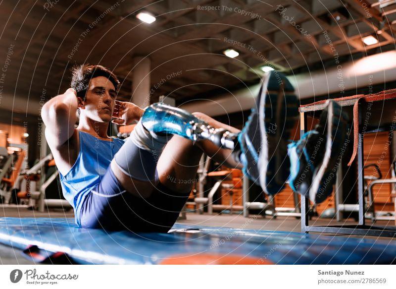 Behinderter junger Mann beim Training in der Turnhalle Jugendliche Athlet Sport prothetisch deaktiviert abdominal paralympisch Fitness Sporthalle Aktion Beine