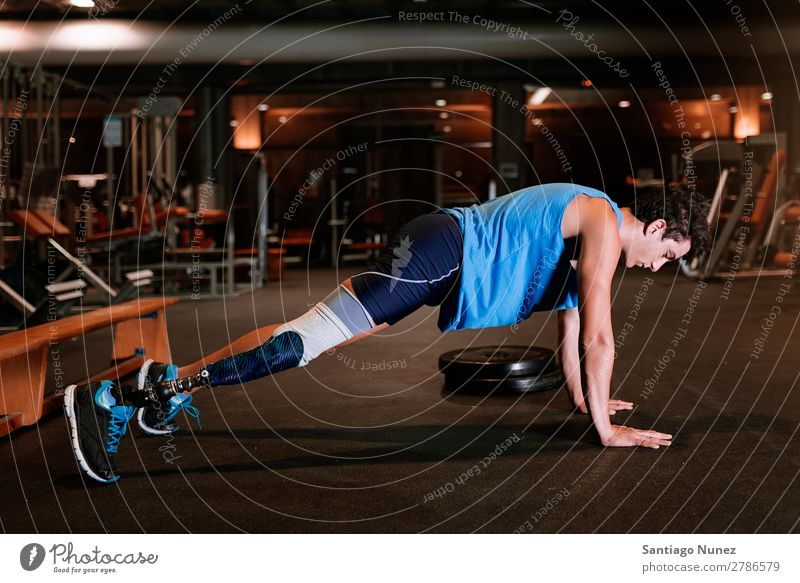Behinderter junger Mann beim Training in der Turnhalle. Jugendliche Athlet Sport prothetisch deaktiviert hochschieben Fitness Sporthalle Aktion Beine amputieren