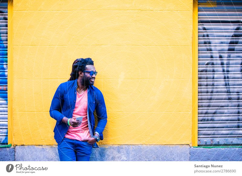 Afrikanischer junger Mann mit Handy auf der Straße. Lifestyle hören schwarz Amerikaner Stadt Porträt Telefon PDA Mobile Solarzelle Mitteilung Texten E-Mail