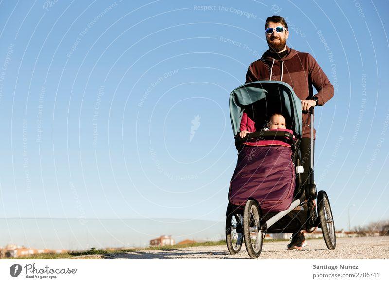 Vater und Sohn laufen im Park. Kinderwagen Joggen rennen Buggy (Motorrad) Familie & Verwandtschaft Baby Jugendliche Tochter Außenaufnahme schön üben Natur