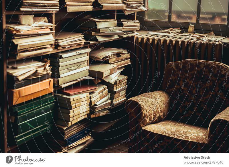 Alter Sessel in Regalnähe mit vielen Papieren Haufen Zusammensetzung Archiv altehrwürdig Schriftstück Raum Anhäufung Mitarbeiter Typ Beruf Literatur Möbel