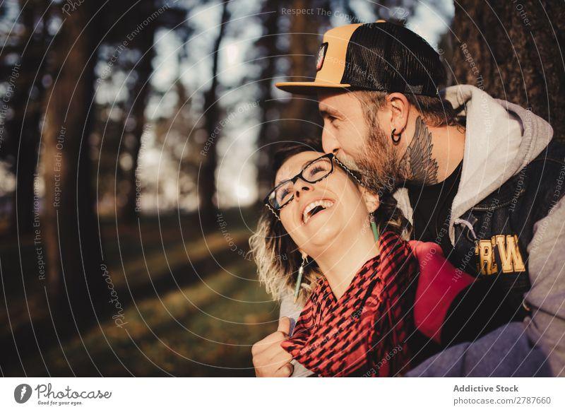 Ein glückliches Paar, das sich am Baum im Park umarmt. Umarmen Glück umarmend Rücken Holz Wald Jugendliche heiter bärtig Mann Frau Freude Schickimicki laufen