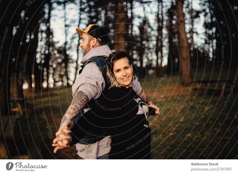 Junger Mann und glückliche Dame stehen Rücken an Rücken im Wald. Paar Tattoo Schnappschuss Park Glück Händchenhalten Typ Jugendliche Schickimicki Lächeln Frau
