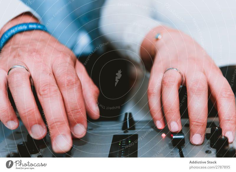 Crop Mann mit Musik-Equalizer benutzend Audio Klang Diskjockey Gerät Hemd Hand Getränk professionell Technik & Technologie Produzent Studioaufnahme elektronisch