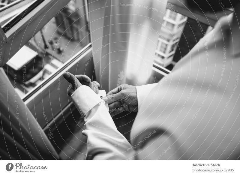 Mann knöpft Hemdärmel zu Hülse zuknöpfend Hand weiß Fenster Bekleidung Mode Design Textil anhaben Stil elegant Baumwolle lässig Knöpfe Stoff Sauberkeit formell