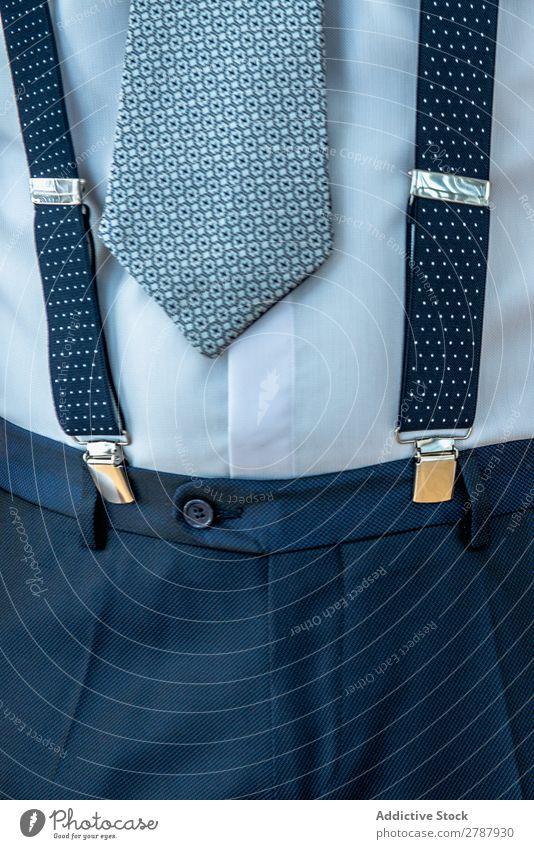 Mann mit Hosenträgern an Hose und Krawatte Blick anhaben Anzug Entwurf blau Hemd Stil Mode Bekleidung Accessoire trendy formell elegant Stoff modisch Design