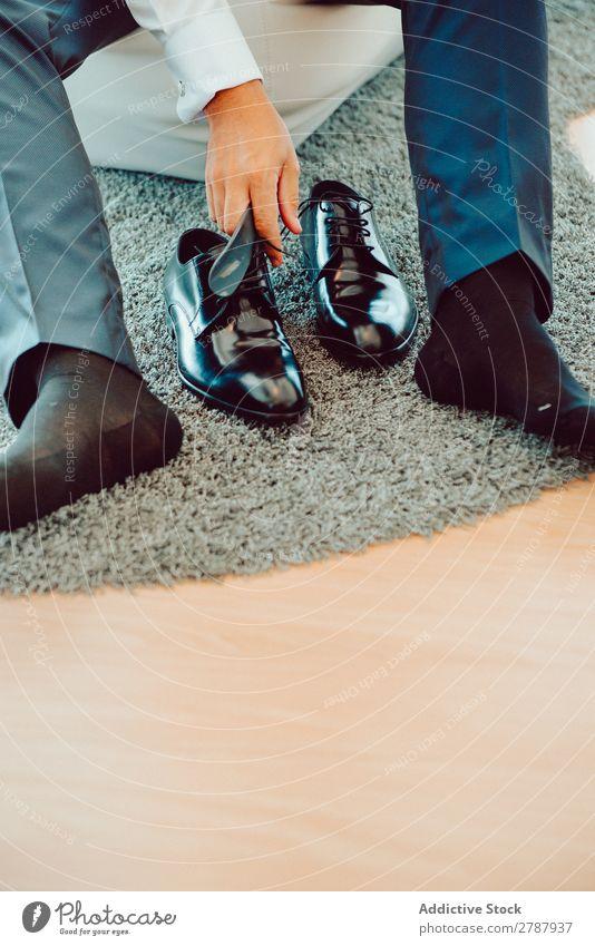 Mann in eleganten Stiefeln anhaben Teppich schwarz Hose sitzen Mode Leder Stil Fuß Design Blick Schuhe klassisch paarweise Konsistenz Unterlage formell Typ