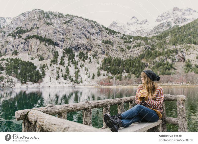 Frau auf Sitz in der Nähe des wunderschönen Sees zwischen den Hügeln im Schnee Pyrenäen wunderbar Wasser
