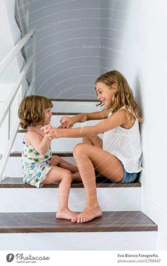 Porträt von zwei glücklichen Kindern, die auf der Treppe sitzen. Lifestyle Freude schön Leben Freizeit & Hobby Spielen Haus Schule Mensch feminin Baby Mädchen