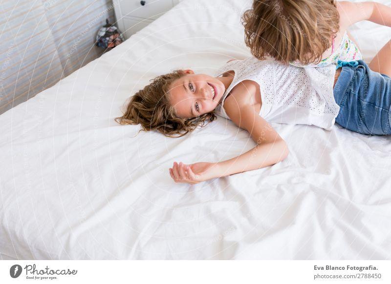 Zwei schöne Schwestern, die auf dem Bett spielen. Lifestyle Freude Freizeit & Hobby Spielen Sommer Haus Schlafzimmer Kind Mensch feminin Baby Kleinkind Mädchen