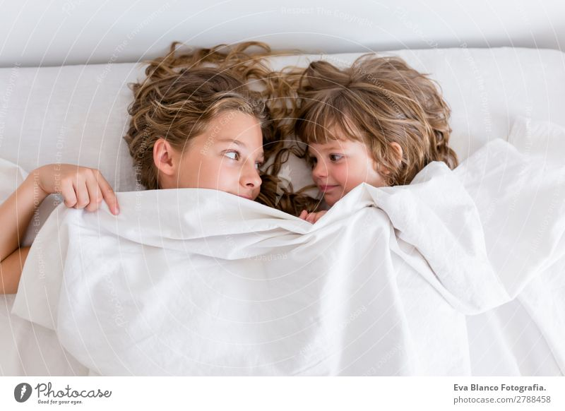 zwei kleine schöne Kinder, die sich auf dem Bett ausruhen. Lifestyle Freude Erholung Freizeit & Hobby Spielen Haus Schulkind Schüler Mensch feminin Baby