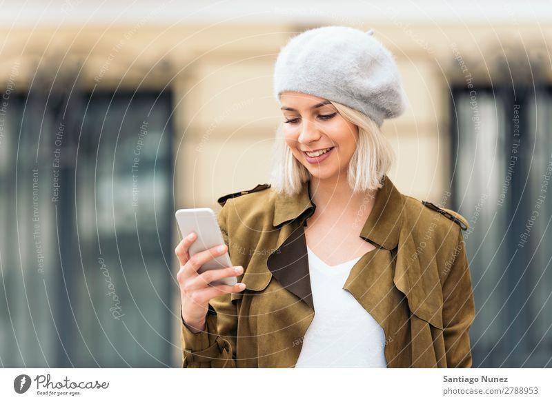 Porträt einer jungen Frau mit ihrem Handy. Jugendliche blond Glück Mädchen schön benutzend Mobile Telefon Mitteilung schreibend Außenaufnahme attraktiv Lächeln