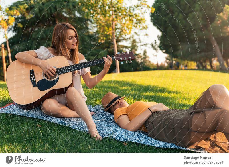 Schöne Frauen, die Spaß am Gitarrespielen im Park haben. Picknick Freundschaft Jugendliche Glück Gitarrenspieler Sommer Mensch Freude Spielen Musik Erwachsene