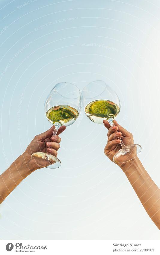 Weibliche Freunde jubeln, wenn sie an die Gläser mit Weißwein stoßen. Wein Paar Toastbrot klirrend heiter Zuprosten Glas Hand Frau Glück Hintergrundbild