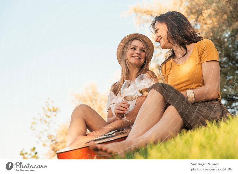 Schöne Frauen, die im Park Wein trinken. Picknick Freundschaft Jugendliche Glück Glas Gitarre Gitarrenspieler Sommer Mensch Freude Musik Erwachsene Mädchen