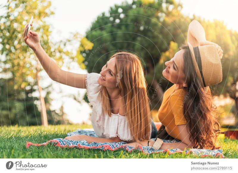 Wunderschöne Frauen, die ein Selbstporträt im Park machen. Picknick Freundschaft Jugendliche Glück Sommer Mensch Freude Mobile PDA Telefon Solarzelle Fotografie