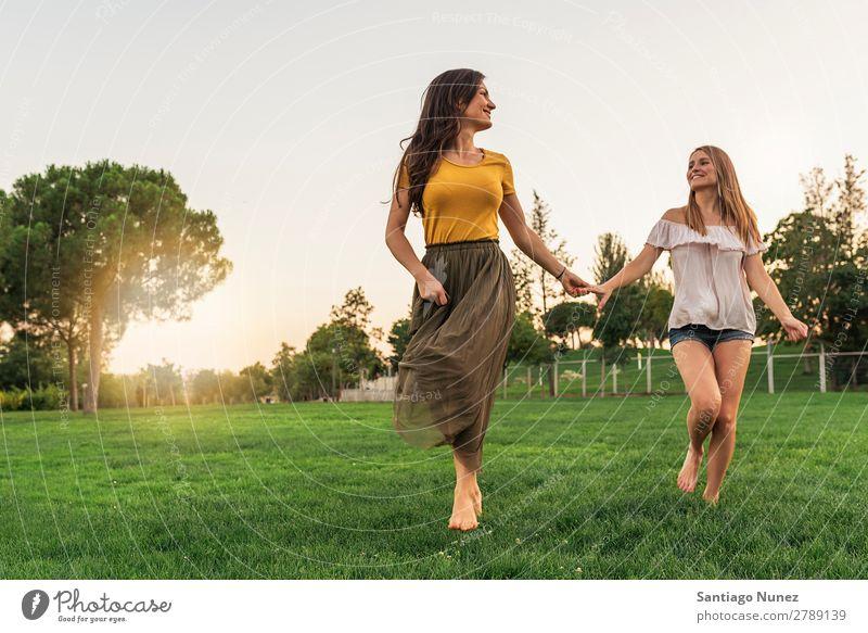 Schöne Frauen lächeln und Spaß haben und laufen. Picknick Freundschaft Jugendliche rennen Hand Spielen Park Glück Sommer Mensch Freude Erwachsene Mädchen hübsch