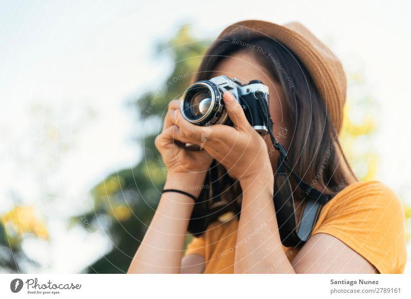 Junge Frau, die eine Kamera benutzt, um ein Foto zu machen. Fotograf Fotografie Fotokamera Jugendliche Mädchen digital weiß Freizeit & Hobby 1 nehmen analog
