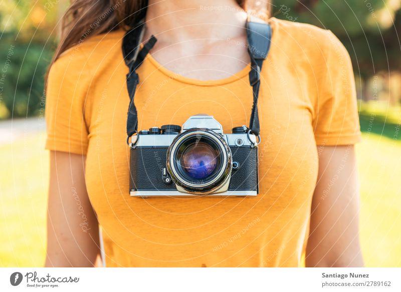 Nahaufnahme eines Fotografen mit seiner Kamera. Fotokamera professionell Fotografie analog Tasche lässig Freizeitkleidung reflektorisch kaukasische Ethnizität