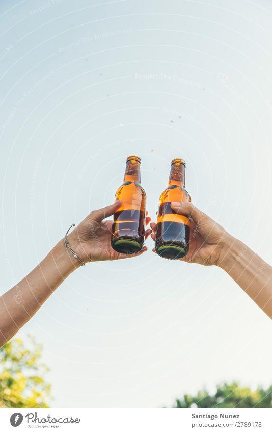 Weibliche Freunde jubeln über klirrende Flaschen Bier. Paar Toastbrot heiter Zuprosten Glas Hand Frau Glück Hintergrundbild Feste & Feiern Fröhlichkeit neu Tag