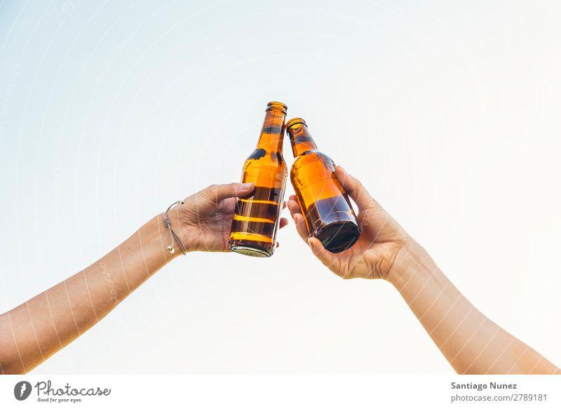 Weibliche Freunde jubeln, wenn klirrende Bierflaschen in den Händen liegen. Paar Toastbrot heiter Zuprosten Glas Flasche Hand Frau Glück Hintergrundbild