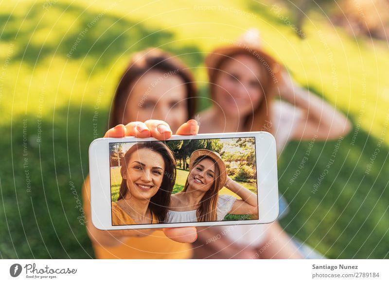 Wunderschöne Frauen, die im Park ein Selbstporträt machen. Picknick Freundschaft Jugendliche Glück Sommer Mensch Freude Mobile PDA Telefon Solarzelle Fotografie