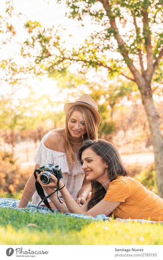 Fotografin, die ihrer Freundin ein Bild zeigt. Frau Picknick Freundschaft Jugendliche Park Glück Fotokamera Gitarre Gitarrenspieler Sitzung Fotografie zeigen