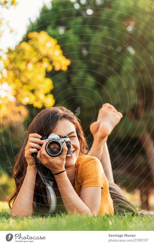 Lächelnde junge Frau, die eine Kamera benutzt, um im Park zu fotografieren. Fotograf Fotografie Fotokamera Jugendliche Mädchen digital weiß Freizeit & Hobby 1