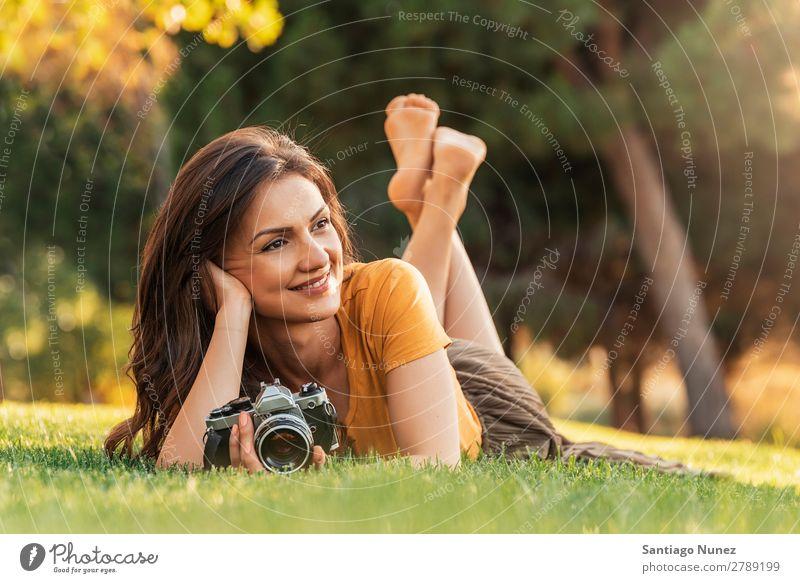 Lächelnde junge Frau, die eine Kamera benutzt, um Fotos zu machen. Fotograf Fotografie Fotokamera Jugendliche Mädchen digital weiß Freizeit & Hobby 1 nehmen