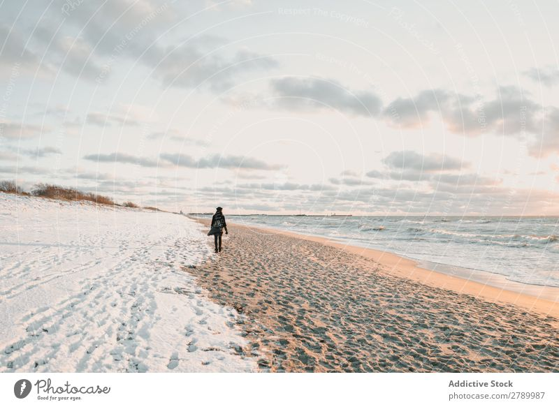 Frau, die an der Schneeküste am Meer spazieren geht. Küste laufen Litauen Klappeda Sand Wasser Mantel Hut Rucksack Natur Winter kalt Frost weiß Lifestyle Dame