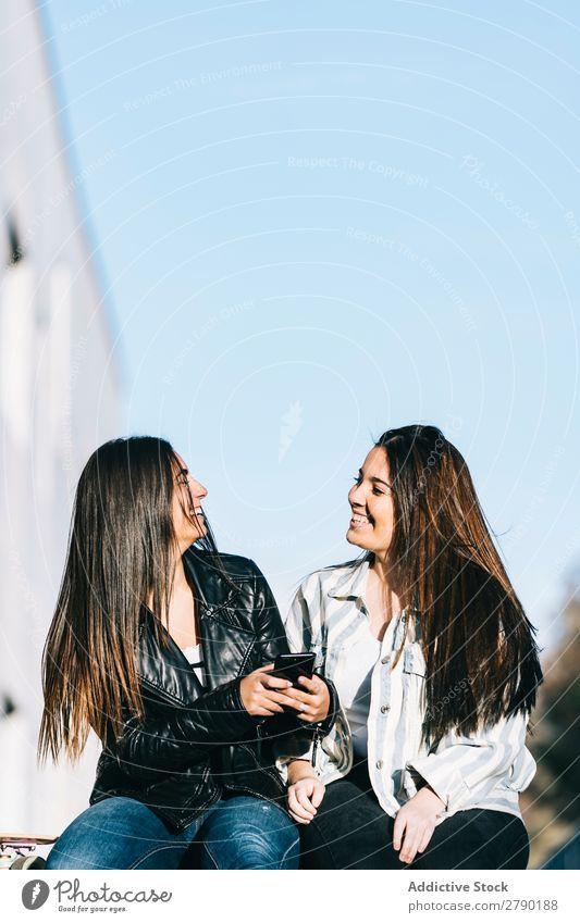 Mädchen, die ein Handy benutzen Wand Technik & Technologie Erwachsene Blick Jugendliche gutaussehend Fensterbrett Teamwork Amerikaner sitzen Freude lässig